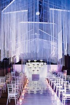 Krzesła w sali ślubnej i miejscu ceremonii ślubnej w kolorze białym i fioletowym