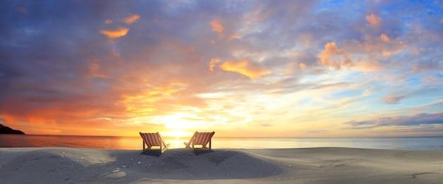 Krzesła w sunset beach. kolorowe niebo o zmierzchu