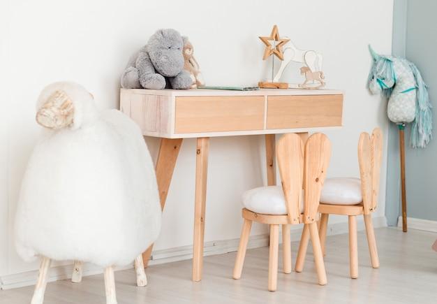 Krzesła z króliczymi uszami w pokoju dziecięcym, stół z zabawkami i duża owca