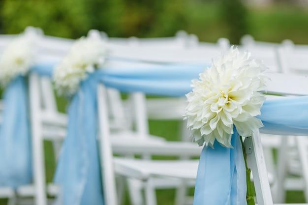 Krzesła ze wstążkami i kwiatami chryzantemy