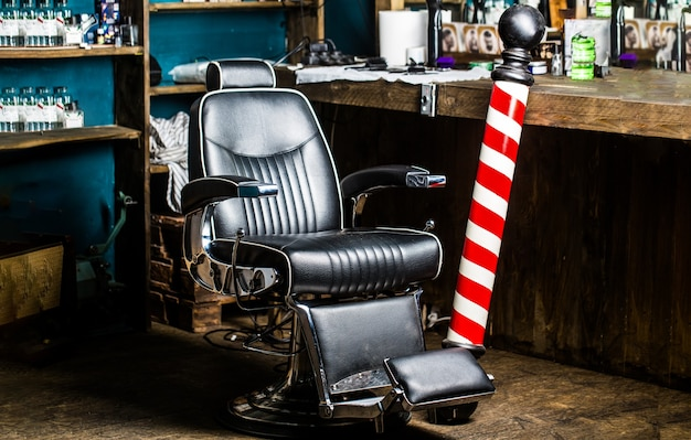 Krzesło fryzjerskie. fotel fryzjerski, salon fryzjerski dla mężczyzn. słup fryzjerski. logo zakładu fryzjerskiego, symbol. stylowe krzesło fryzjerskie w stylu vintage. fryzjer w salonie fryzjerskim.