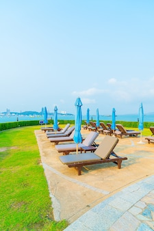 Krzesło i parasol wokół basenu z oceanem