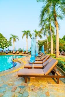 Krzesło i parasol wokół basenu z palmą kokosową