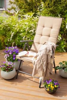 Krzesło ogrodowe na tarasie w słońcu, krzew kwiaty