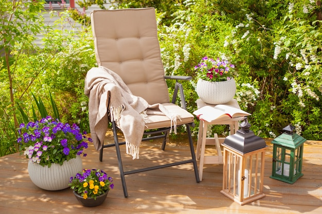 Krzesło ogrodowe na tarasie w słońcu, kwiaty bratek