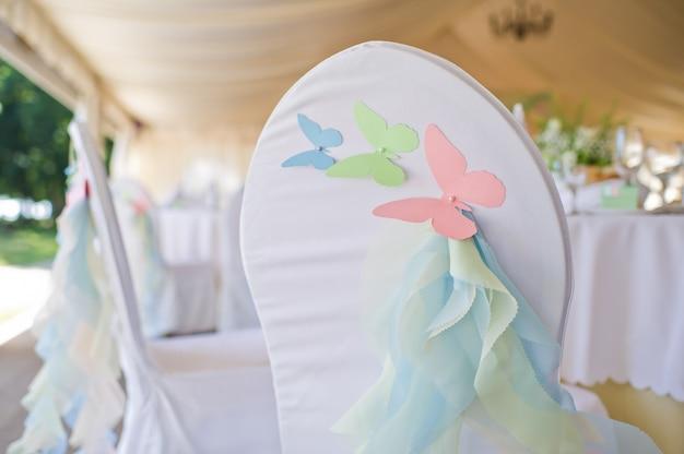 Krzesło ozdobione motylkami wykonanymi z papieru.