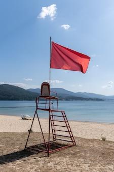 Krzesło ratownika z czerwoną flagą macha. brak koncepcji pływania
