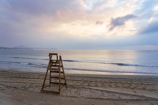 Krzesło ratownika z widokiem na morze o zachodzie słońca ze spokojnym morzem.