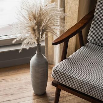 Krzesło retro z połowy wieku i bukiet trawy pampasowej w glinianym garnku na tle okna z zasłonami