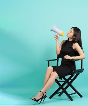 Krzesło reżysera czarny. azjatycka kobieta trzyma megafon i siedzi na krześle. mięta lub tiffany niebieskie tło.