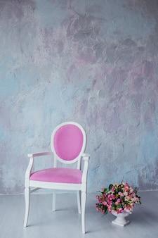 Krzesło vintage z różową tapicerką na szarej ścianie i wazonem z kwiatami. kopiuj przestrzeń