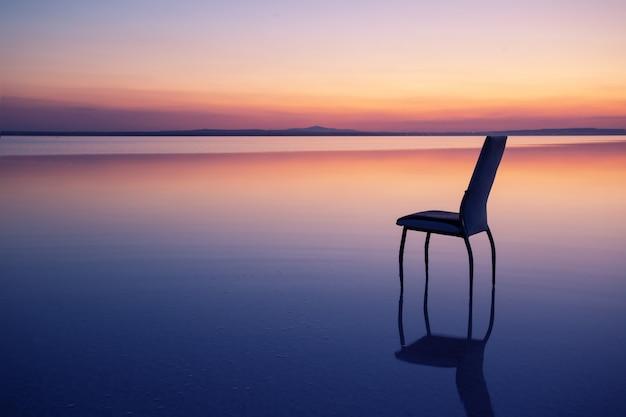 Krzesło w środku jeziora o zachodzie słońca