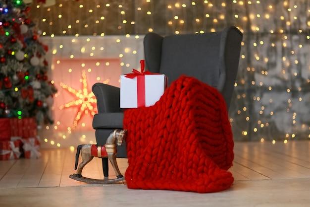 Krzesło z czerwoną ciepłą kratą i pudełkiem przewiązanym świąteczną wstążką