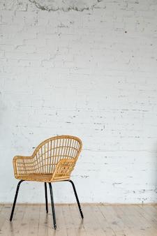 Krzesło z wikliny rattanowej na tle ściany z cegły białej z miejsca na kopię.