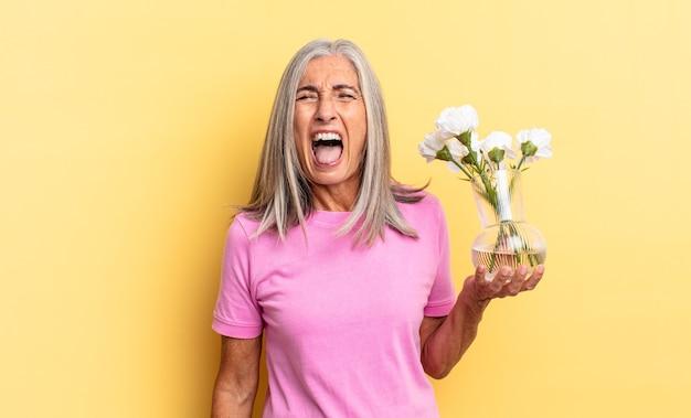 Krzycząc agresywnie, wyglądając na bardzo rozgniewanego, sfrustrowanego, oburzonego lub zirytowanego, krzycząc bez trzymania ozdobnych kwiatów