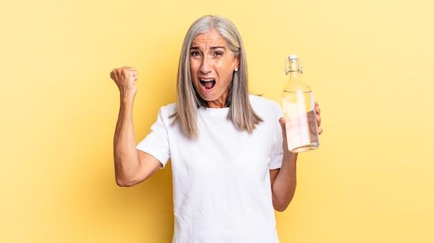 Krzycząc agresywnie z gniewnym wyrazem twarzy lub z zaciśniętymi pięściami świętując sukces i trzymając butelkę wody