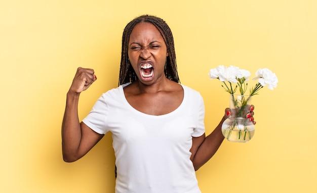 Krzycząc agresywnie z gniewnym wyrazem twarzy lub z zaciśniętymi pięściami świętując sukces. koncepcja dekoracyjnych kwiatów