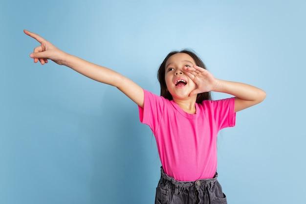 Krzycząc, dzwoniąc. kaukaski portret małej dziewczynki na niebieskiej ścianie.