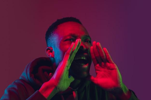 Krzycząc głośno wołając rękami portret afrykańskiego mężczyzny na białym tle na studio gradientu