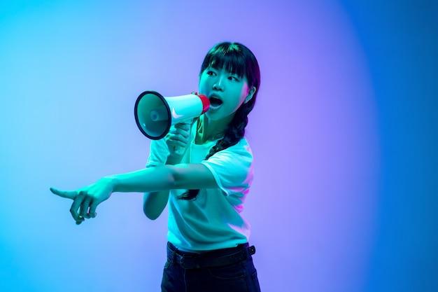 Krzycząc z głośnika. portret młodej kobiety azjatyckie na gradientowym niebiesko-fioletowym tle studio w neon. pojęcie młodości, ludzkie emocje, wyraz twarzy, sprzedaż, reklama. piękna brunetka modelka.