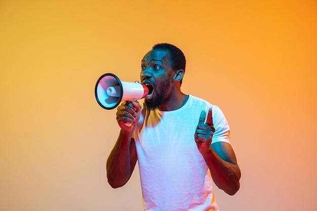 Krzycząc z megafonem. nowoczesny portret afro-amerykanina na gradientowym pomarańczowym tle studio w neon. piękny model afro. pojęcie ludzkich emocji, wyraz twarzy, sprzedaż, reklama. miejsce.