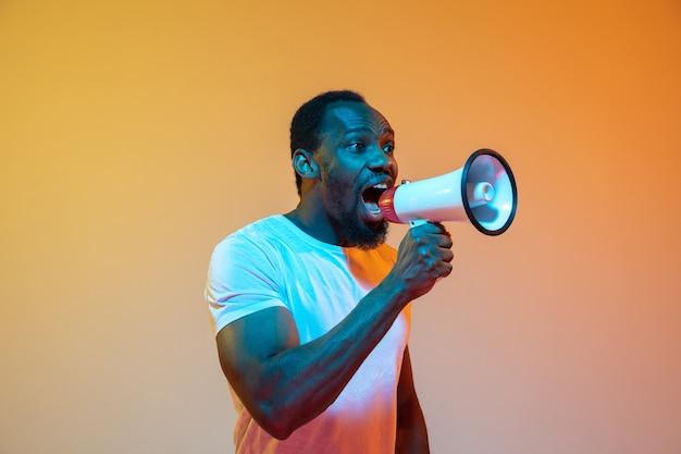 Krzycząc z megafonem. nowoczesny portret afroamerykańskiego mężczyzny na gradientowym pomarańczowym tle studio w neon. piękny model afro. pojęcie ludzkich emocji, wyraz twarzy, sprzedaż, reklama. miejsce.