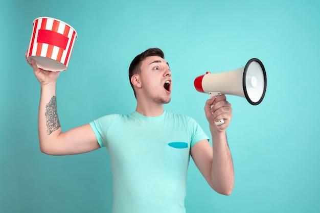 Krzycząc z popcornem. kaukaski portret młodego mężczyzny na niebieskiej ścianie studia