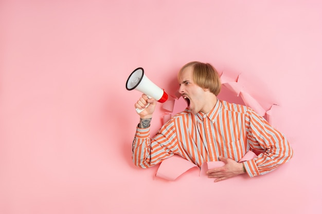 Krzycząc za pomocą głośnika. wesoły kaukaski młody człowiek pozuje w podartym papierze koralowym