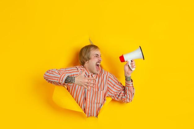 Krzycząc za pomocą głośnika. wesoły kaukaski młody człowiek pozuje w podartym żółtym papierze