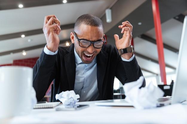 Krzycząc zmęczony biznesmen przy biurku w biurze