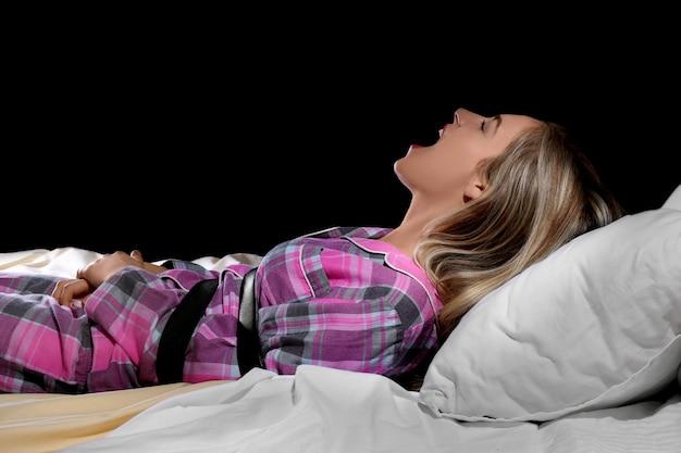 Krzycząca dziewczyna przewiązana paskiem w łóżku. koncepcja paraliżu sennego
