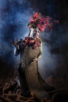 Krzycząca dziewczyna umazana gliną w cementowej sukience. model posiada nakrycie głowy wykonane z kwiatów. dym od tyłu.