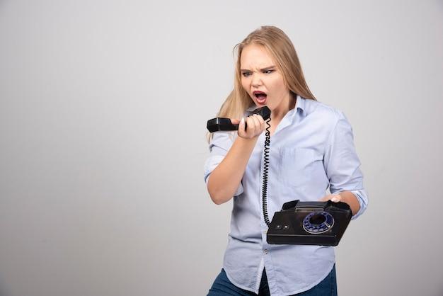 Krzycząca kobieta trzyma telefon i rozmawia na białym tle szarej ścianie.