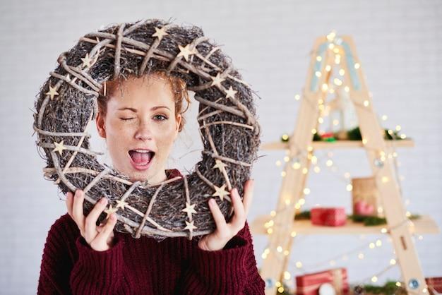 Krzycząca kobieta trzyma wieniec bożonarodzeniowy
