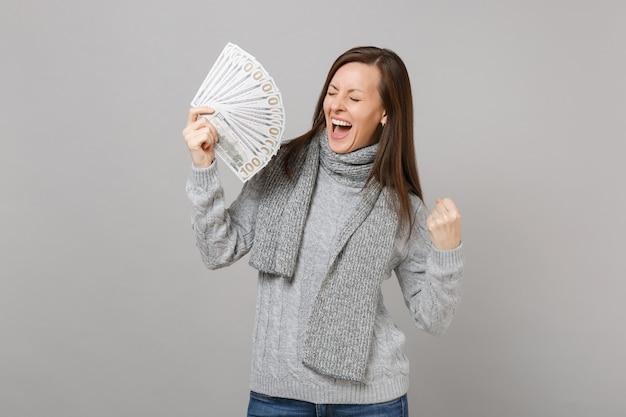Krzycząca kobieta w szarym swetrze, szalik z zamkniętymi oczami robi gest zwycięzcy trzymać wiele dolarów banknotów gotówki na białym tle na szarym tle. styl życia ludzi emocje koncepcja zimnej pory roku.