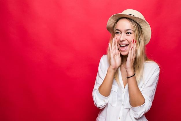 Krzycząca młoda kobieta w słomkowym kapeluszu stojącym na białym tle nad czerwoną ścianą.