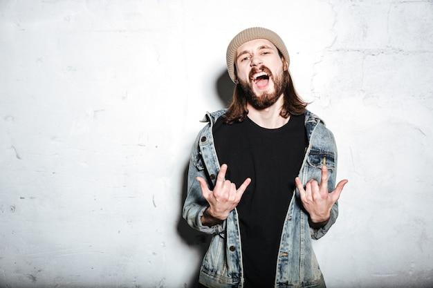 Krzyczący brodaty hipster mężczyzna w kapeluszu ubrany w dżinsową kurtkę pozujący na ścianie, wykonując rockowy gest