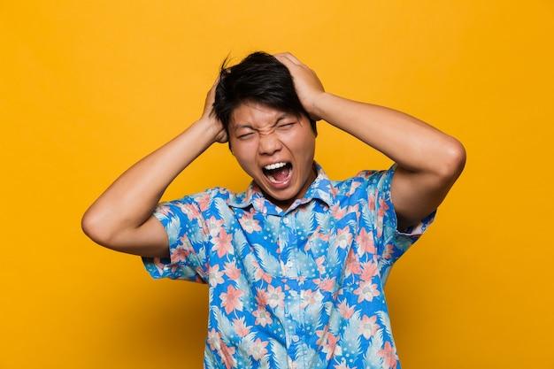 Krzyczący emocjonalny młody człowiek azjatycki pozowanie na białym tle nad żółtą przestrzenią.