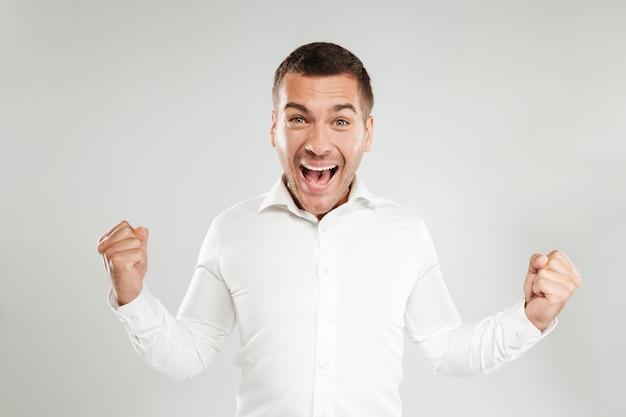 Krzyczący emocjonalny młody człowiek robi zwycięzcy gestowi.
