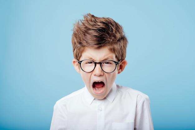Krzyczący mały chłopiec w okularach spójrz w kamerę odizolowaną na niebieskim tle