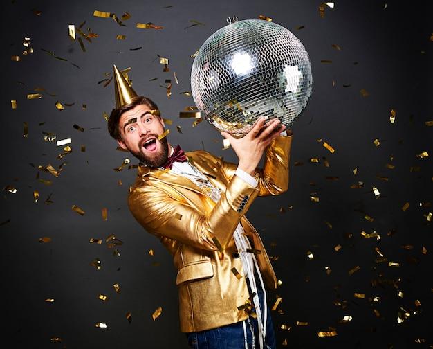Krzyczący mężczyzna trzyma dyskotekę z kapeluszem urodzinowym