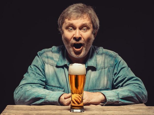 Krzyczący mężczyzna w dżinsowej koszuli ze szklanką piwa