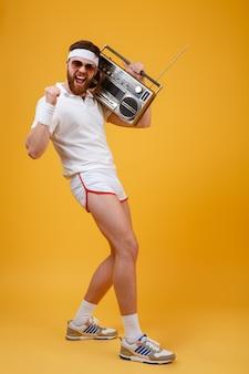 Krzyczący młody człowiek jest ubranym okulary przeciwsłonecznych trzyma magnetofon