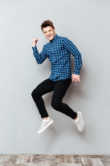 Krzyczący młody człowiek stojący na szarej ścianie i skoki.