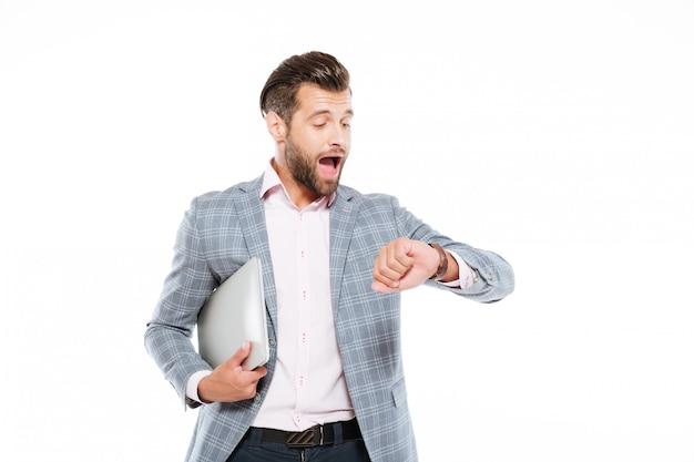 Krzyczący młody człowiek trzyma laptop patrzeje zegarek.