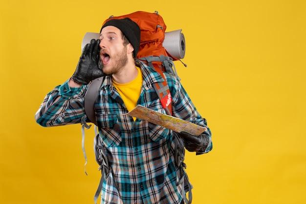 Krzyczący młody turysta w czarnym kapeluszu trzymający mapę