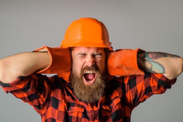 Krzyczący pracownik budowlany brodaty budowniczy w kasku i rękawicach roboczych krzyczący budowniczy w twardym