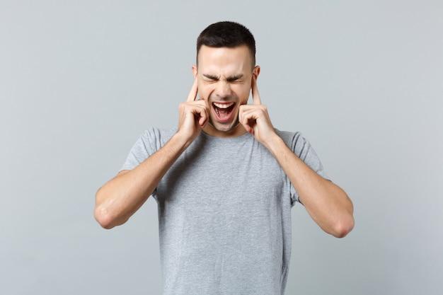 Krzyczący sfrustrowany młody mężczyzna w zwykłych ubraniach, trzymający zamknięte oczy, zakrywający uszy palcami