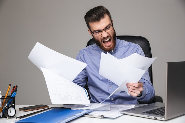 Krzyczący zły brodaty elegancki mężczyzna w okularach czytający dokumenty siedząc przy stole w biurze