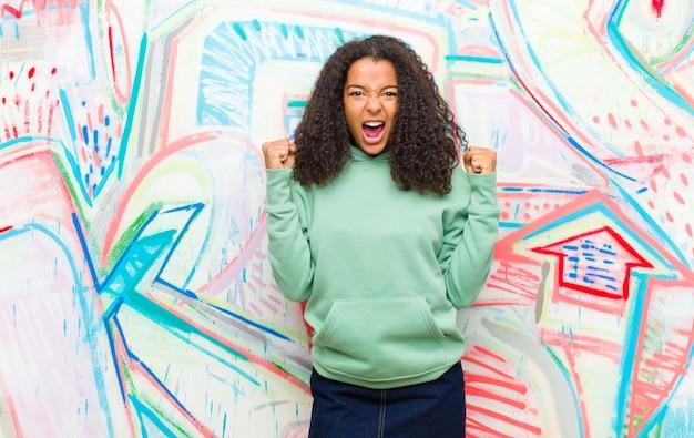 Krzyczeć agresywnie z gniewnym wyrazem twarzy lub zaciśniętymi pięściami, świętując sukces